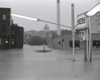 An emergency worker in a rowboat paddles out onto Cameron Street.