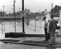 Mayor Swenson, along with Mrs. Swenson and Constable Ed Watson, survey the flood damage from Berryhill Street near Cameron Street.
