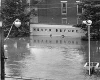 A half-submerged billboard on South Cameron Street proclaims the message Never Before...